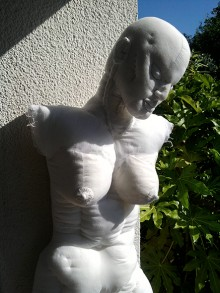 Head and upper body photograph of Koure the female white soft sculpture figure, outside in the sunshine whith white wall and shades of green Fatsia Japonica