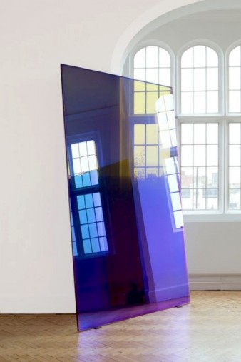 photo of plate of mirrored glass installed in a white gallery space, reflecting a row of victorian windows in the background