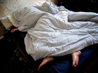 photo of a blue striped duvet covering an unseen person.