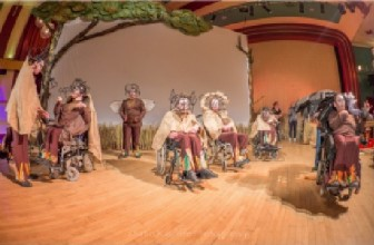 A group of disabled actors, some of whom are in wheelchairs on stage performing Clive Essame's Impisi