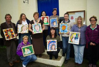photo shows a group of people holding self-portrait paintings