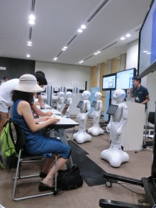 Five white robots, each with what looks like an ipad on its chest, are stood before a line of students sitting at desks. A female student in a blue dress and white hat is in the foreground. Behind the robots is a teacher with microphone and at least three