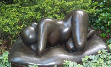 Bronze sculpture of a naked woman lying on her side amide greenery.