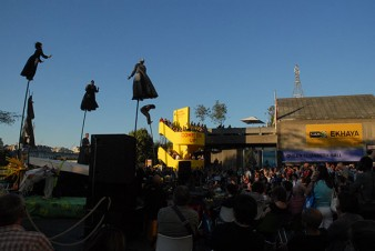 Crowd watching outdoor theatre production including cloaked people on moving poles
