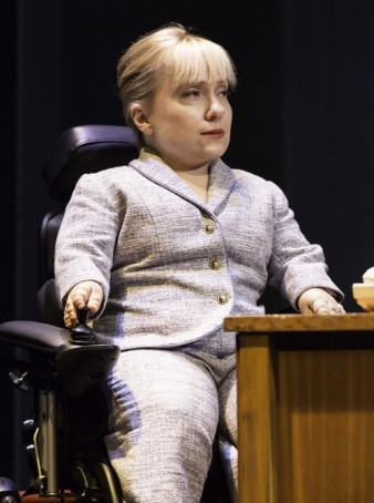 photo of actress Kiruna Stamell pictured at a desk and wearing a smart suit
