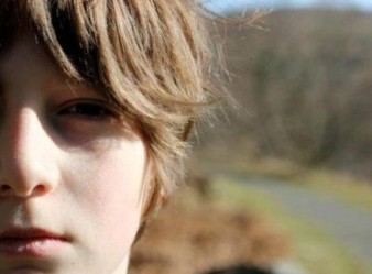 a close up photograph of a boy's face against a rural landscape