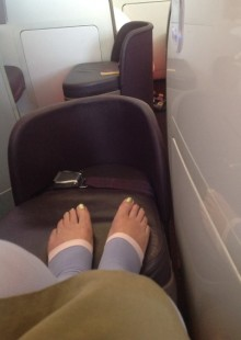 my toes, complete with gold nail varnish, proped up on the footstool at the end of my seat in the first class part of the plane. The decor is grey metal and plastic, the seating black leather (?) and apart from my toes my legs are encased in blue and whit